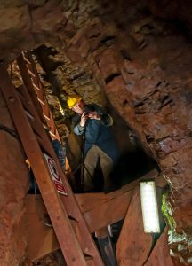 Chris Dewar from Soundview up a ladder with a camera on location at VR video tour shoot Geevor Tin Mine