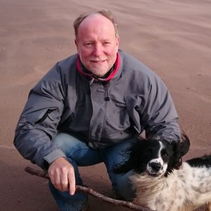 Tourism leader Robin Barker of Services for Tourism, with dog on beach